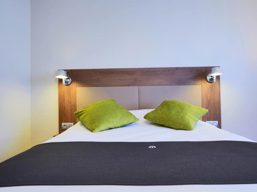 A bed or beds in a room at Campanile Bordeaux Ouest - Mérignac Aéroport