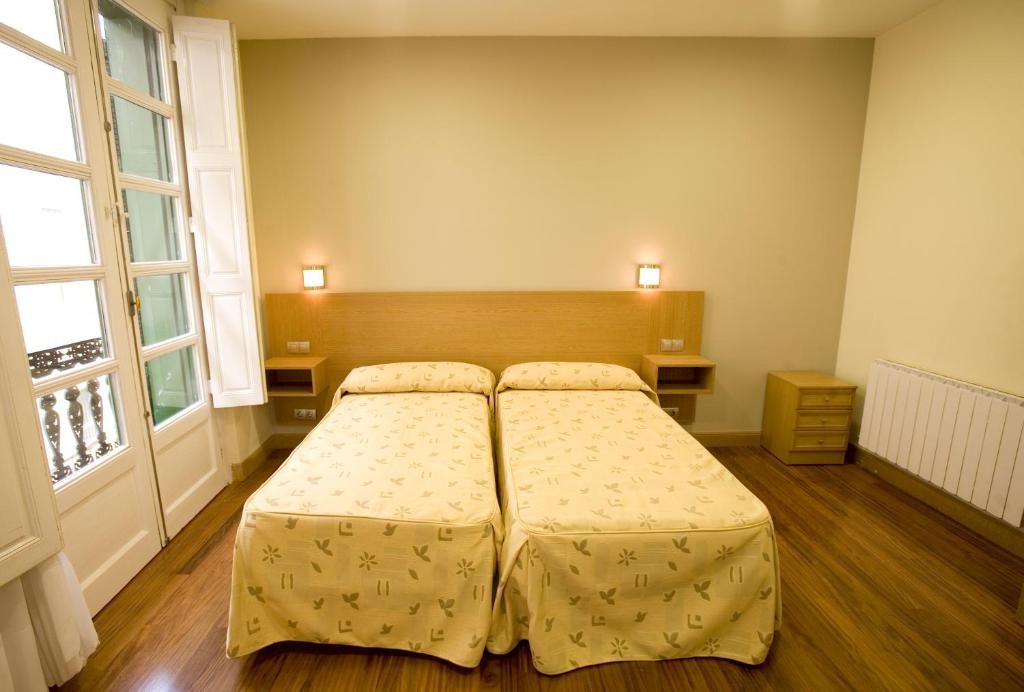 A bed or beds in a room at Roquefer Bilbao Central Rooms