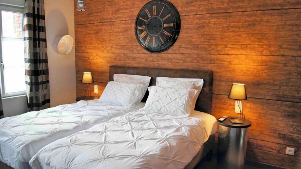 A bed or beds in a room at Les Béthunoises - Suites design, Spa et Sauna