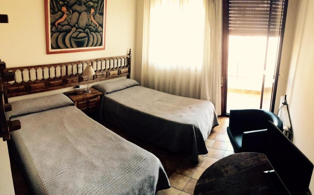 A bed or beds in a room at Hostal Mimosa
