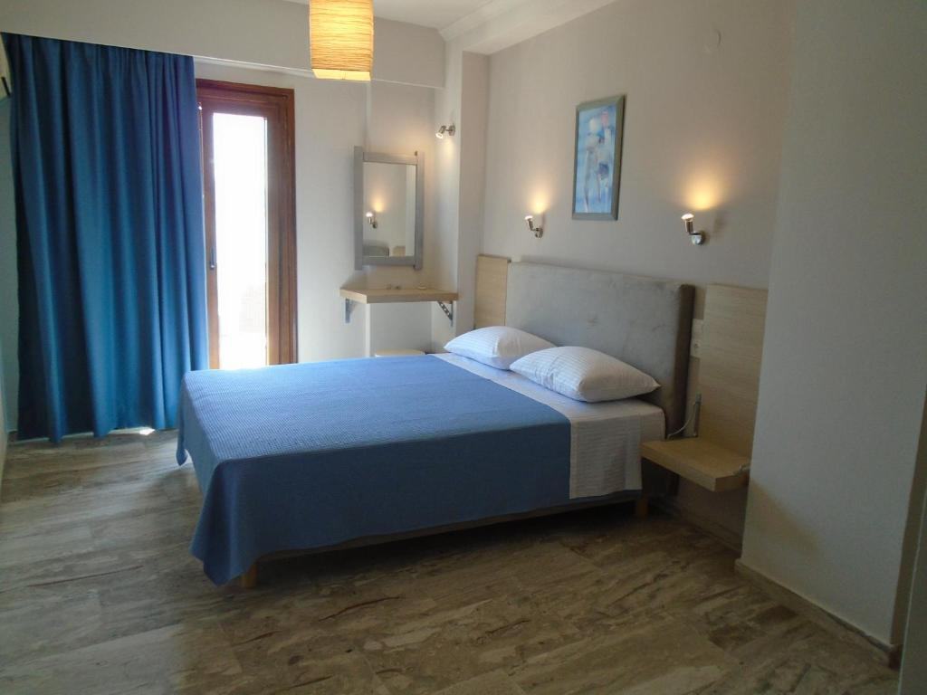 A bed or beds in a room at Polyxeni Hotel