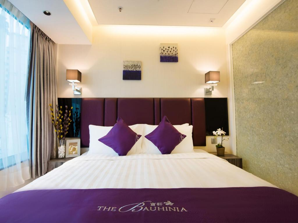 A bed or beds in a room at The Bauhinia Hotel - Tsim Sha Tsui