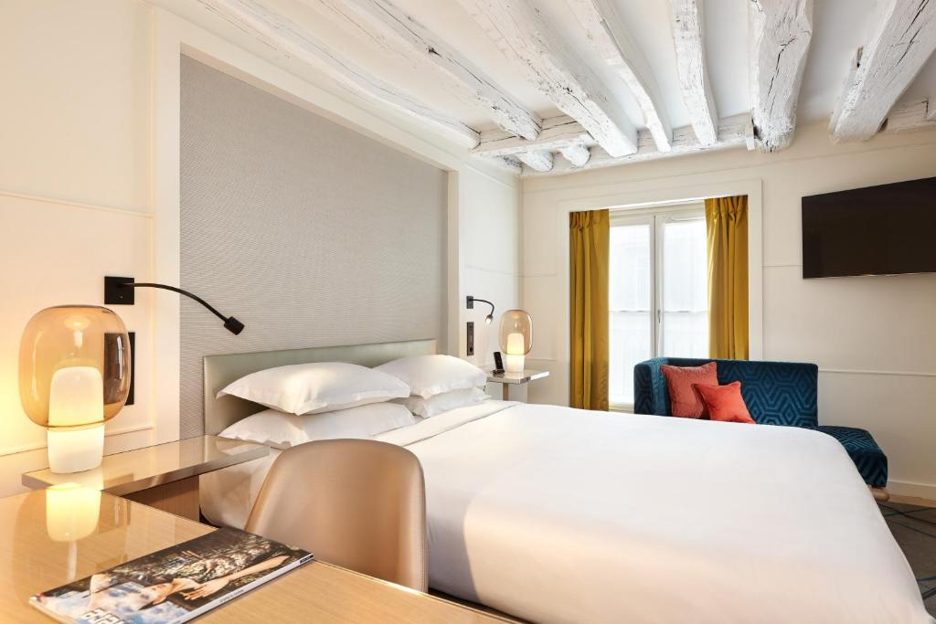 A bed or beds in a room at Hotel Opéra Richepanse