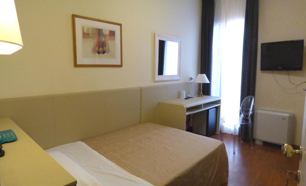 Ein Bett oder Betten in einem Zimmer der Unterkunft Hotel Centrale Byron