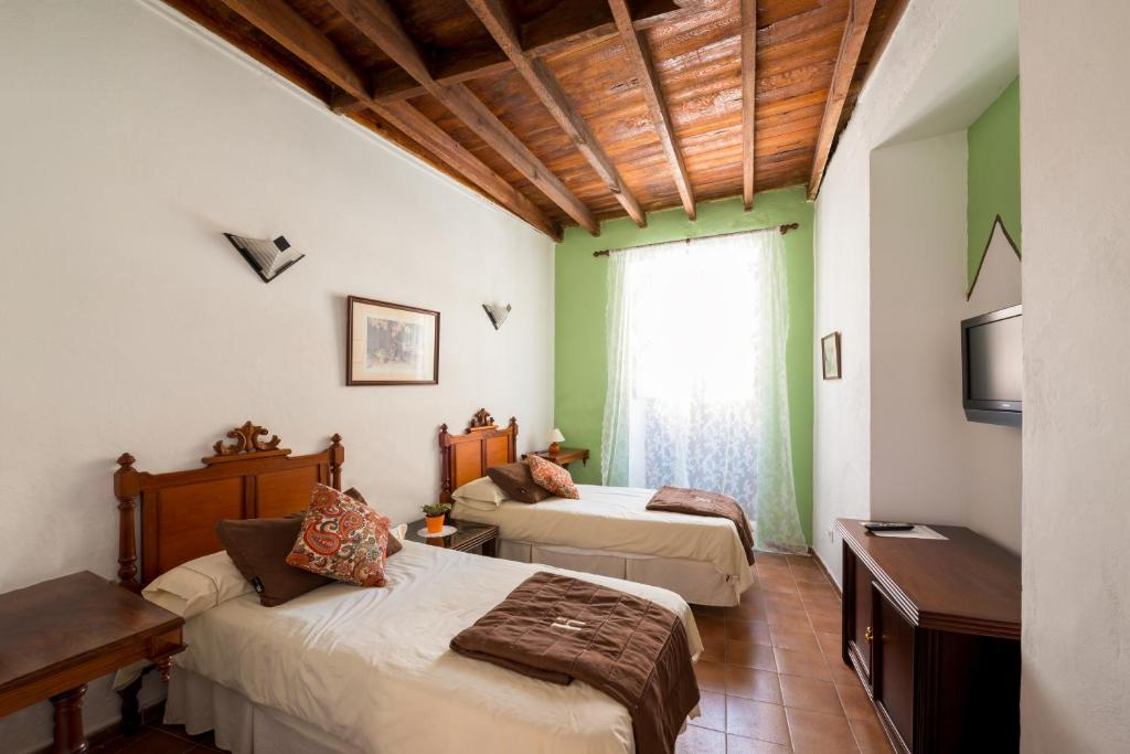 A bed or beds in a room at Hotel Rural Villa Agüimes