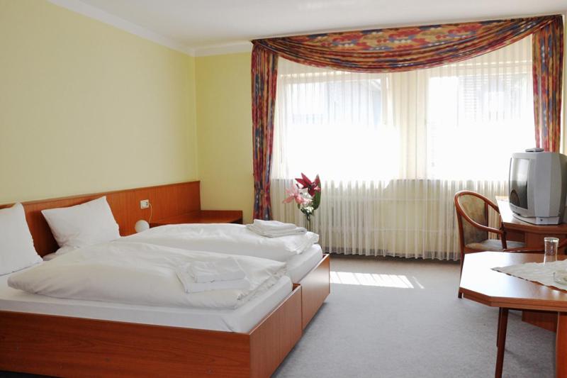 Ein Bett oder Betten in einem Zimmer der Unterkunft Hotel Hessischer Hof