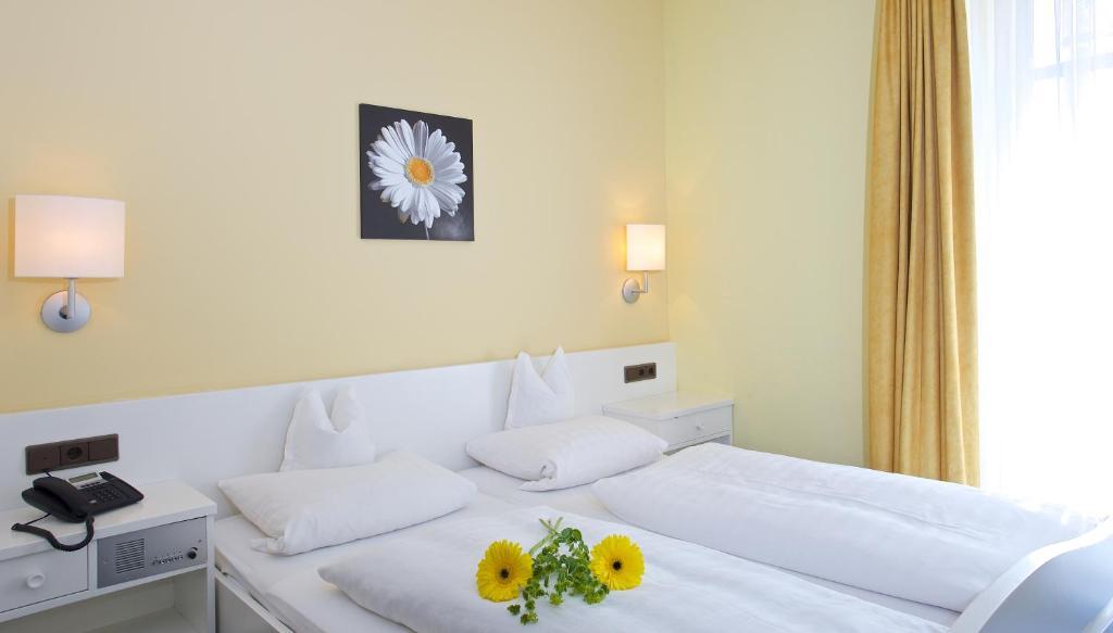 A bed or beds in a room at Hotel Garni Herdegen
