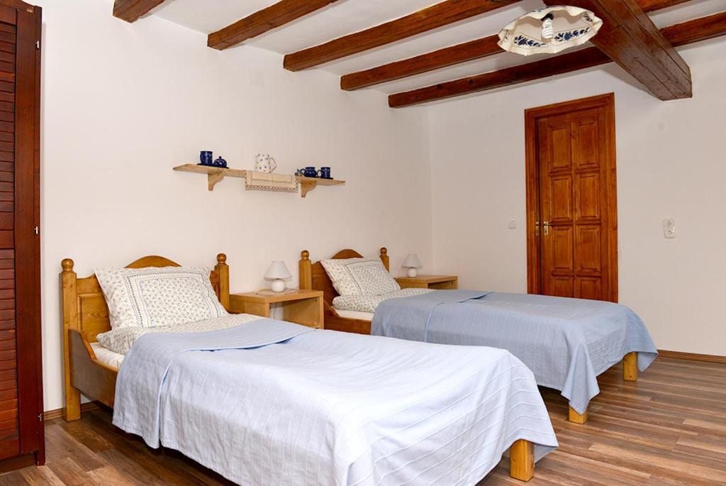 A bed or beds in a room at Rigófütty Vendégház