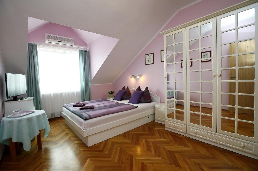 A bed or beds in a room at Cecey Vendégház