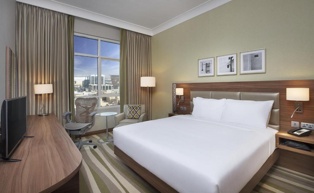 A bed or beds in a room at Hilton Garden Inn Dubai Al Muraqabat - Deira