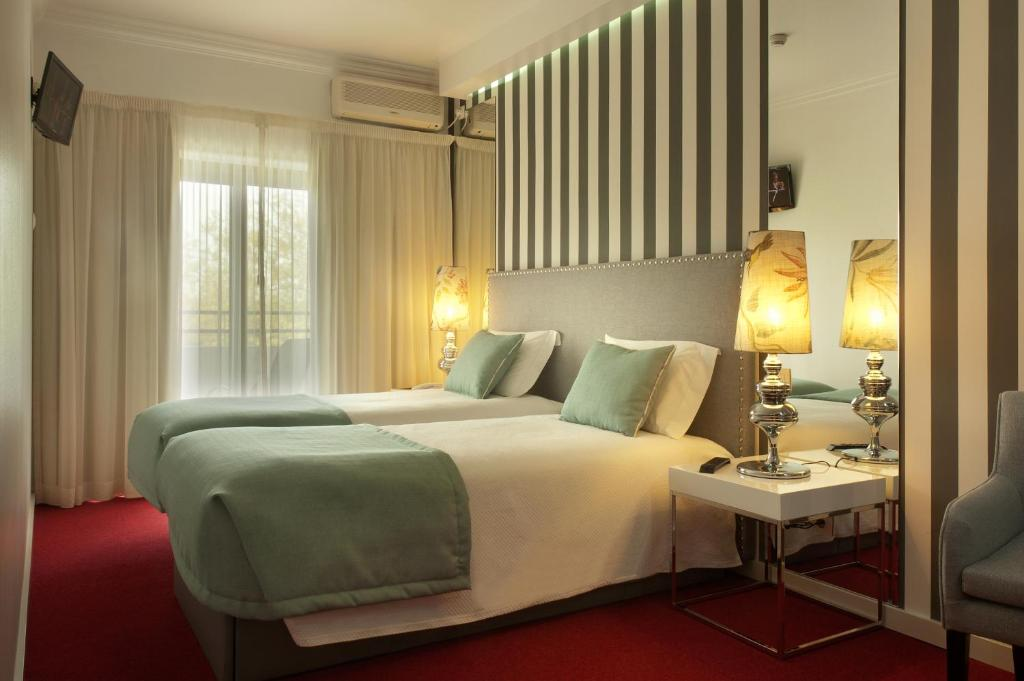 A bed or beds in a room at Hotel Lagoa dos Pastorinhos