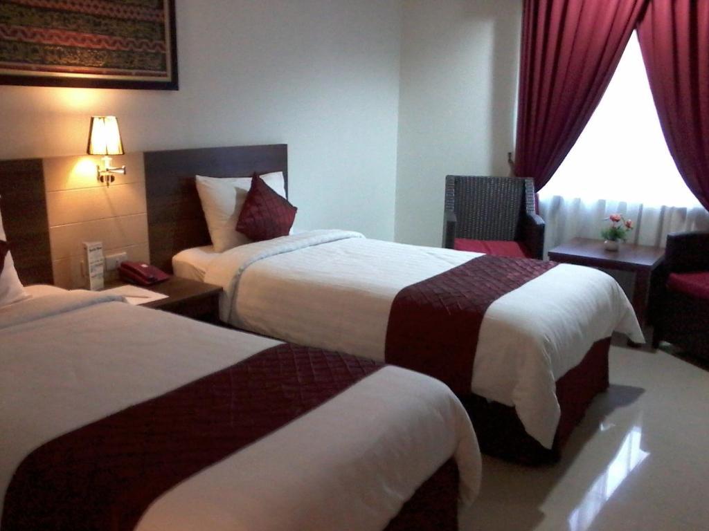 A bed or beds in a room at Hotel Bandara Syariah