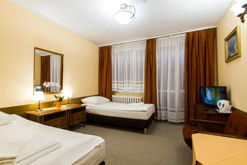 A bed or beds in a room at Hotel PRL RZEMIEŚLNIK