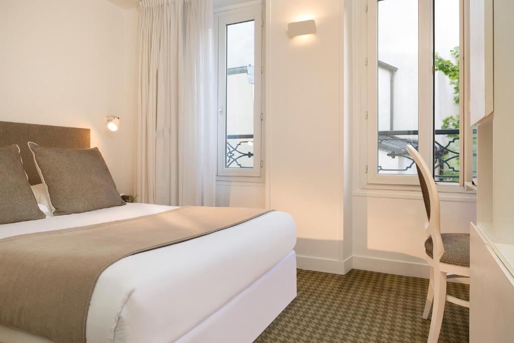 A bed or beds in a room at Hôtel Mistral