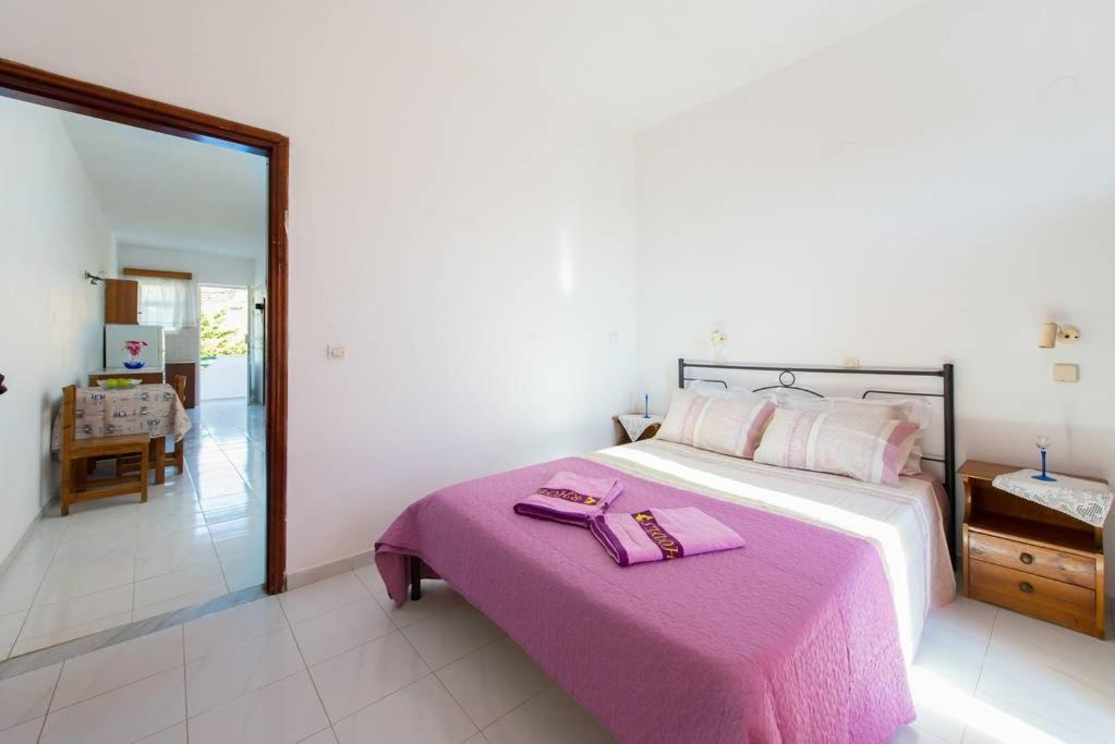 A bed or beds in a room at Merryland Studios & Apartments