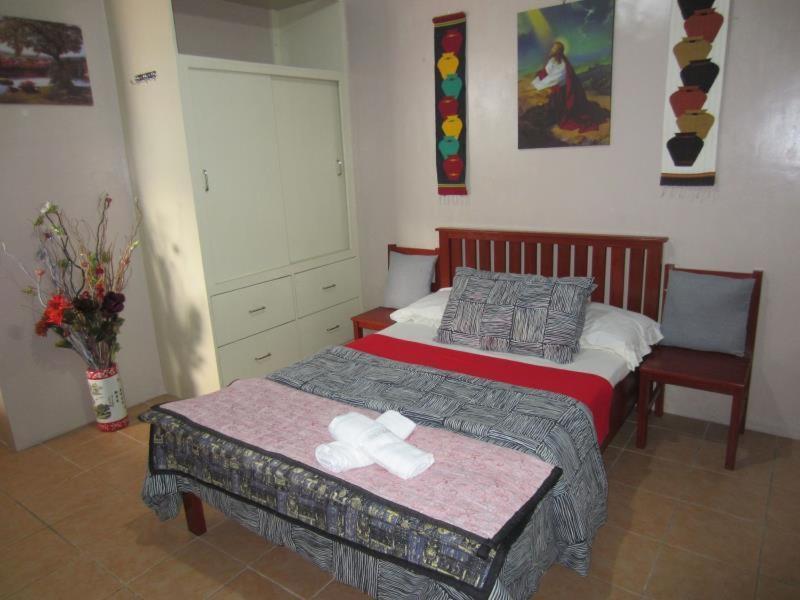 A bed or beds in a room at Lyn's Do Drop Inn Transient House