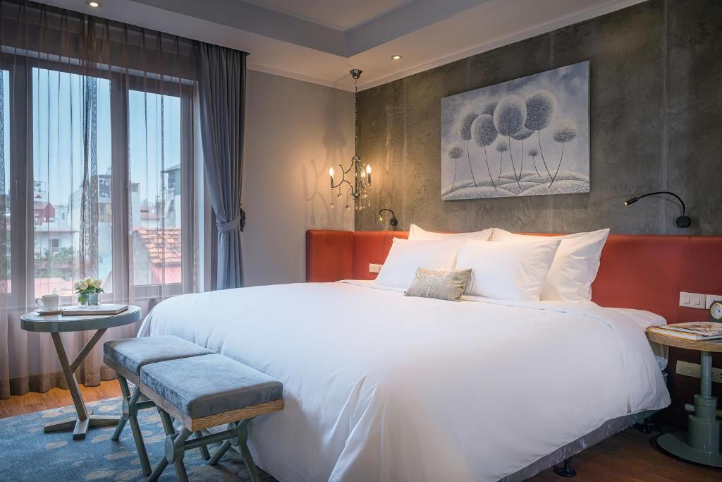 A bed or beds in a room at Hanoi La Siesta Hotel Trendy