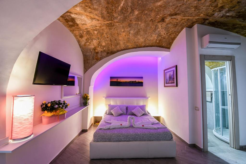 A bed or beds in a room at Petros Room Camere