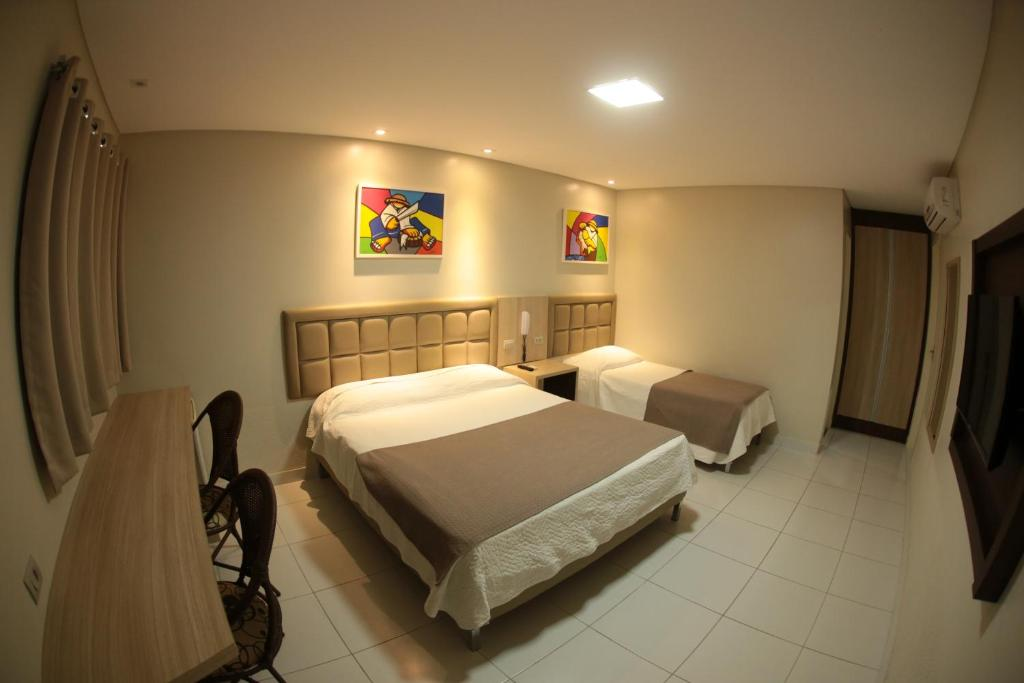A bed or beds in a room at Caruaru Park Hotel