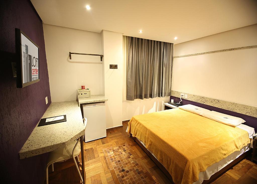 A bed or beds in a room at Center Verdes Pássaros Loft