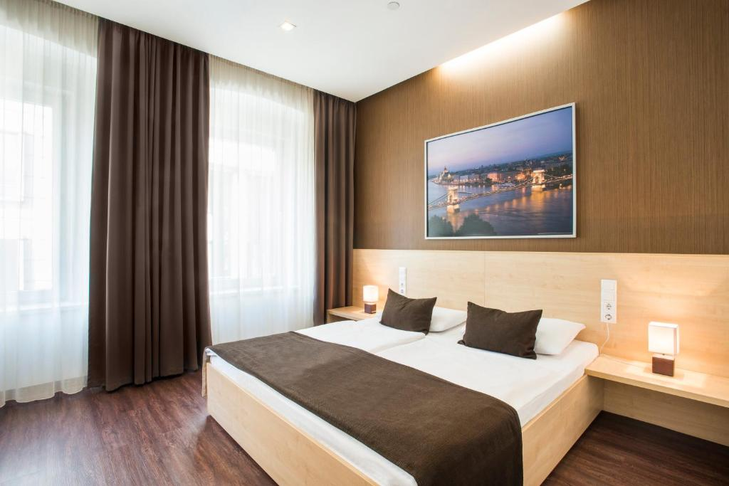 A bed or beds in a room at Promenade City Hotel