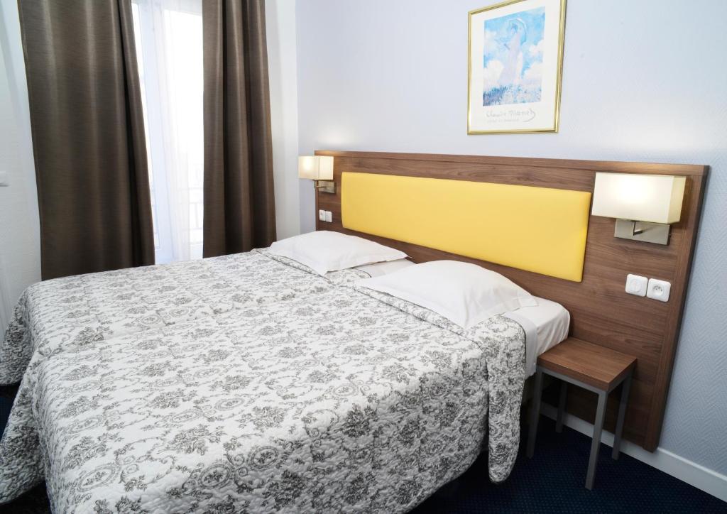 Кровать или кровати в номере Hôtel Ambassadeur