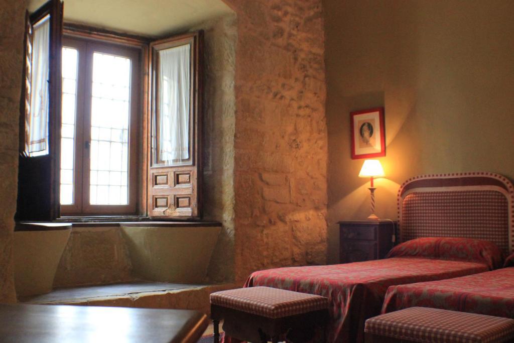 A bed or beds in a room at Casa Palacio Conde de Garcinarro