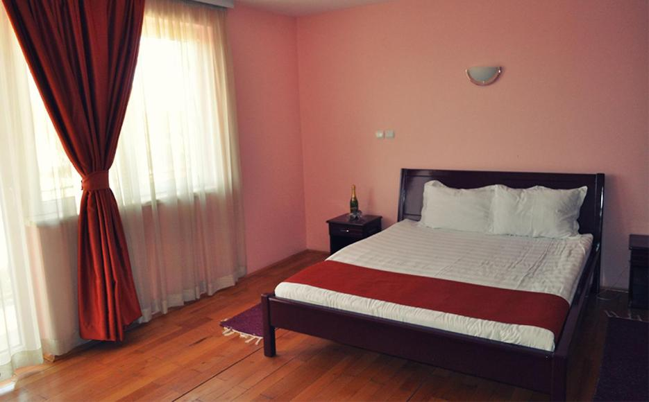 A bed or beds in a room at Hotel Satelit Kumanovo