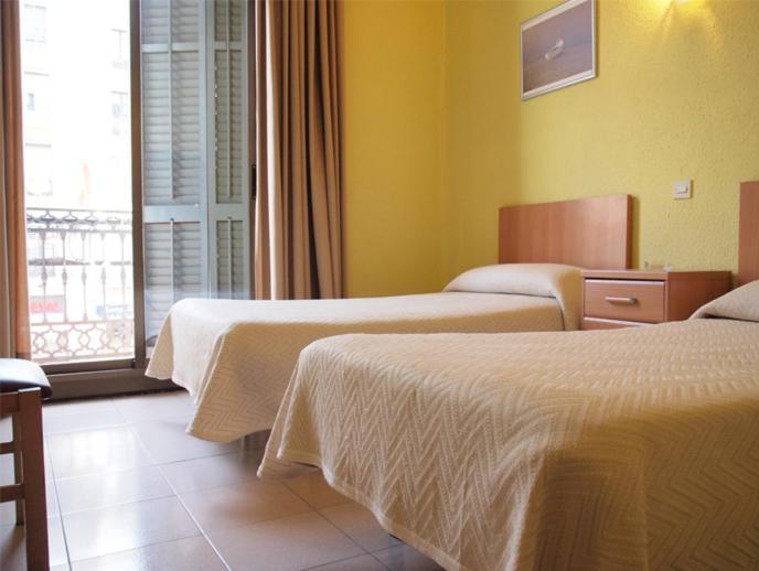 Un ou plusieurs lits dans un hébergement de l'établissement Hostal Delfos
