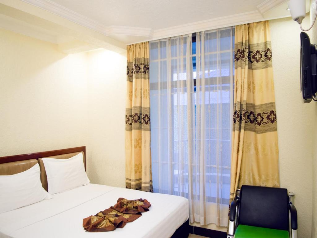A bed or beds in a room at Best Point Hotel