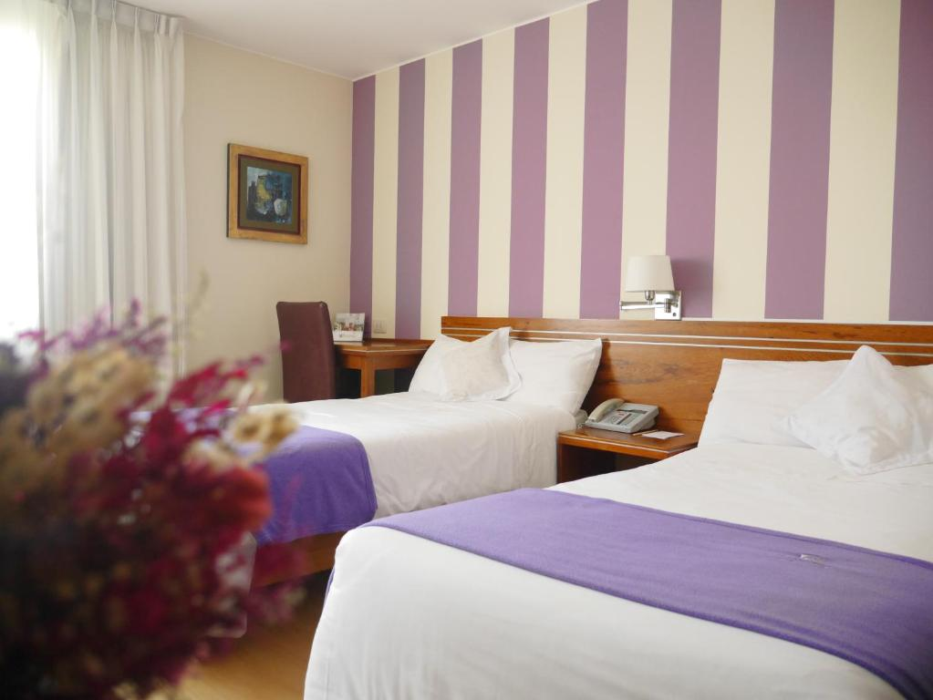 A bed or beds in a room at Hotel Runcu Miraflores