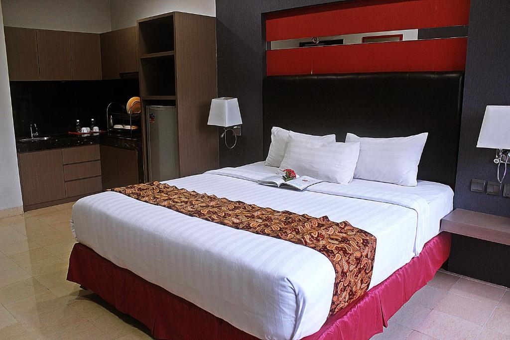 A bed or beds in a room at The Centro Hotel & Residence By Orchardz