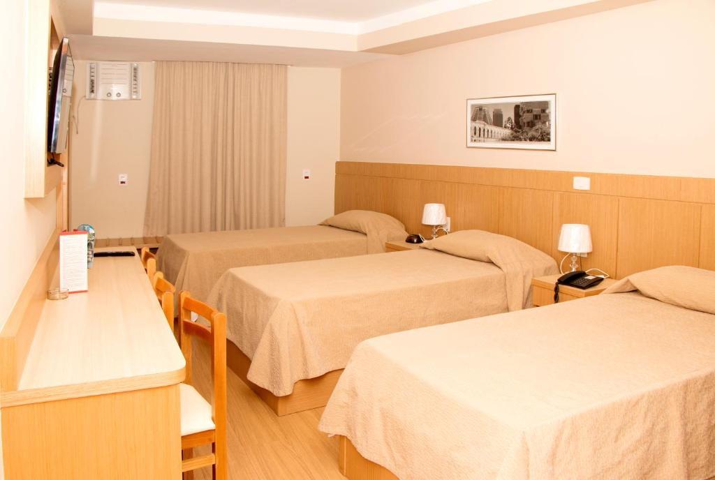 A bed or beds in a room at Hotel Pouso Real