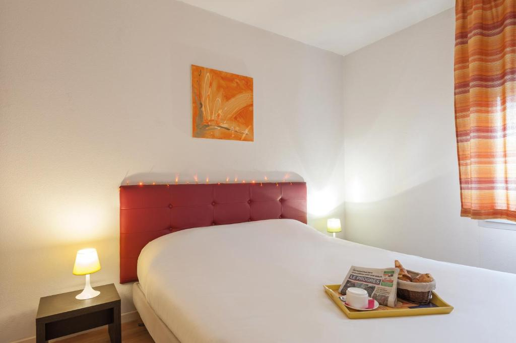 A bed or beds in a room at Appart'City Bourg en Bresse