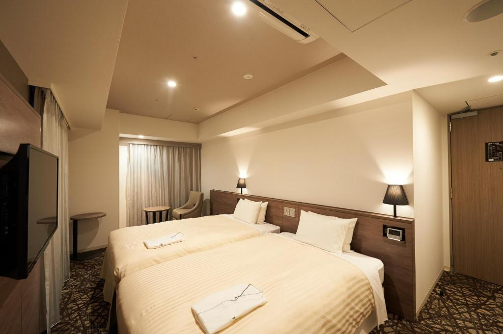 A bed or beds in a room at Sotetsu Fresa Inn Ginza-Nanachome