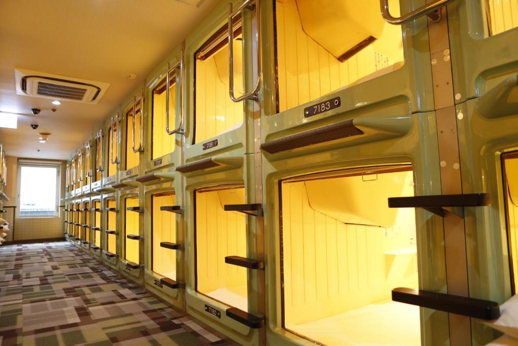 A bunk bed or bunk beds in a room at Shinjuku Kuyakusho-mae Capsule Hotel