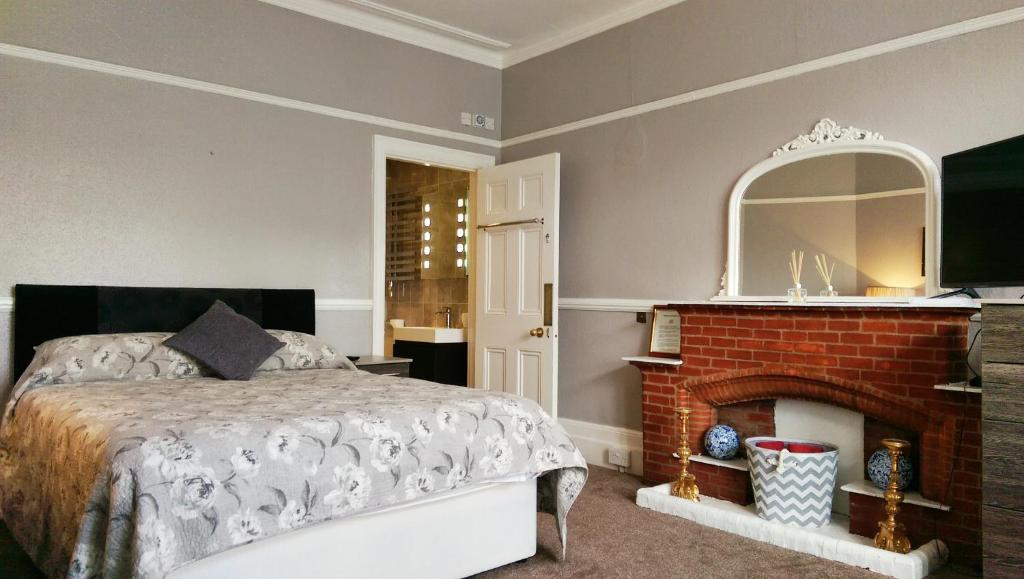 A bed or beds in a room at Glendevon House Hotel