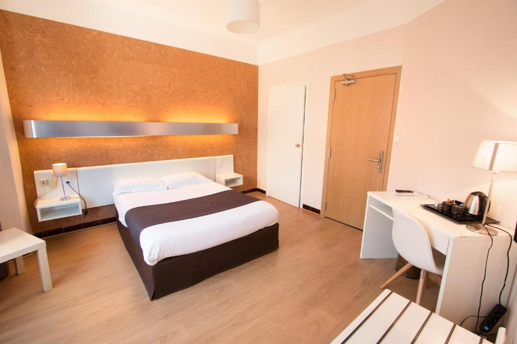 A bed or beds in a room at Hôtel Mondial