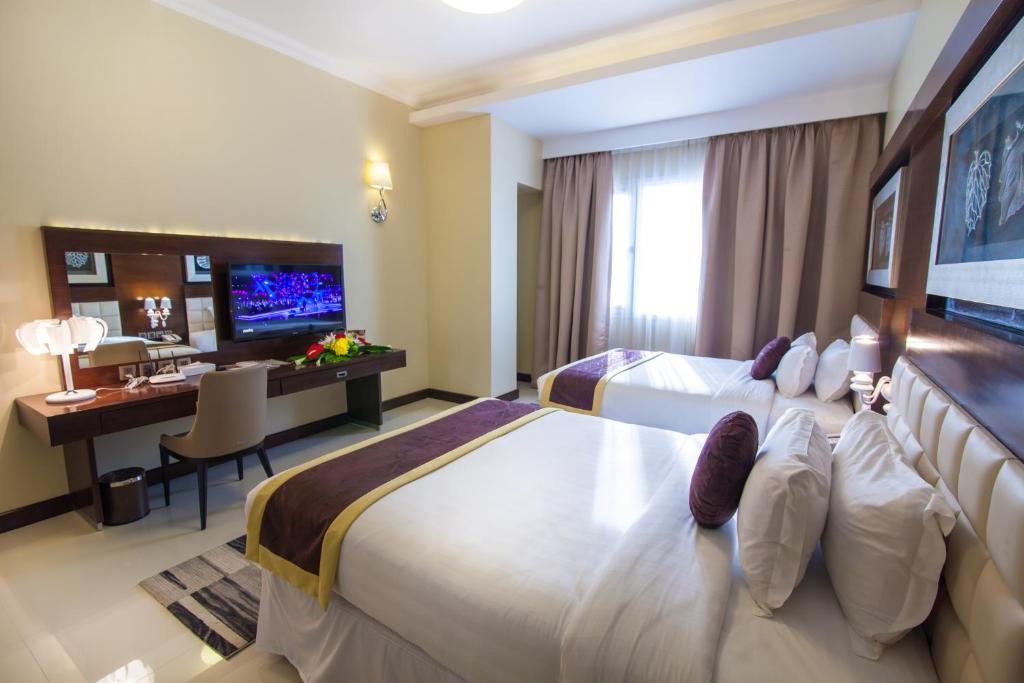 سرير أو أسرّة في غرفة في فندق اتيرام بريمير