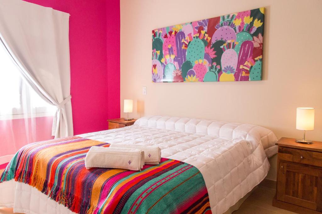 Una cama o camas en una habitación de Las Tulmas Apart Hotel