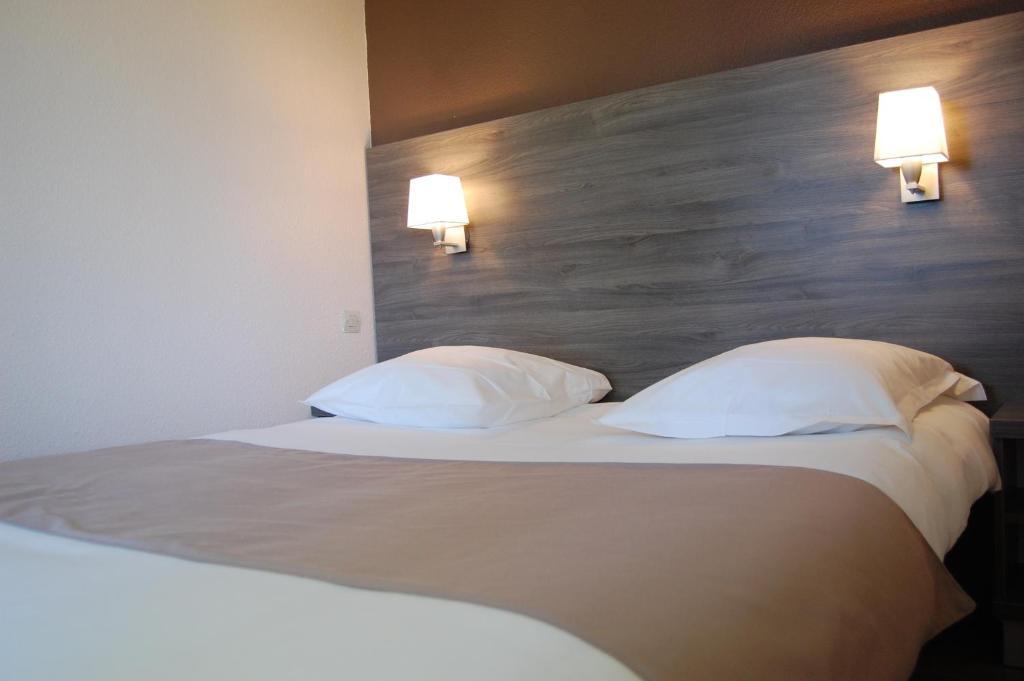 A bed or beds in a room at Hotel Restaurant Des Portes De Meuse