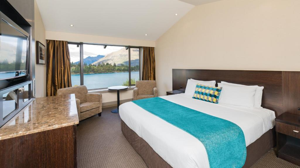 A bed or beds in a room at Copthorne Hotel & Resort Lakefront Queenstown
