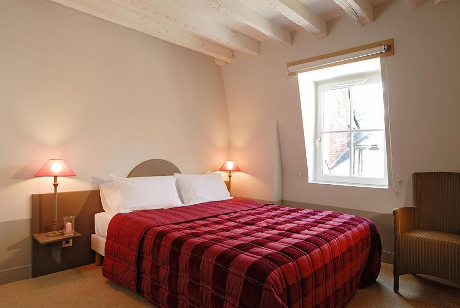 A bed or beds in a room at Hôtel L'Adresse