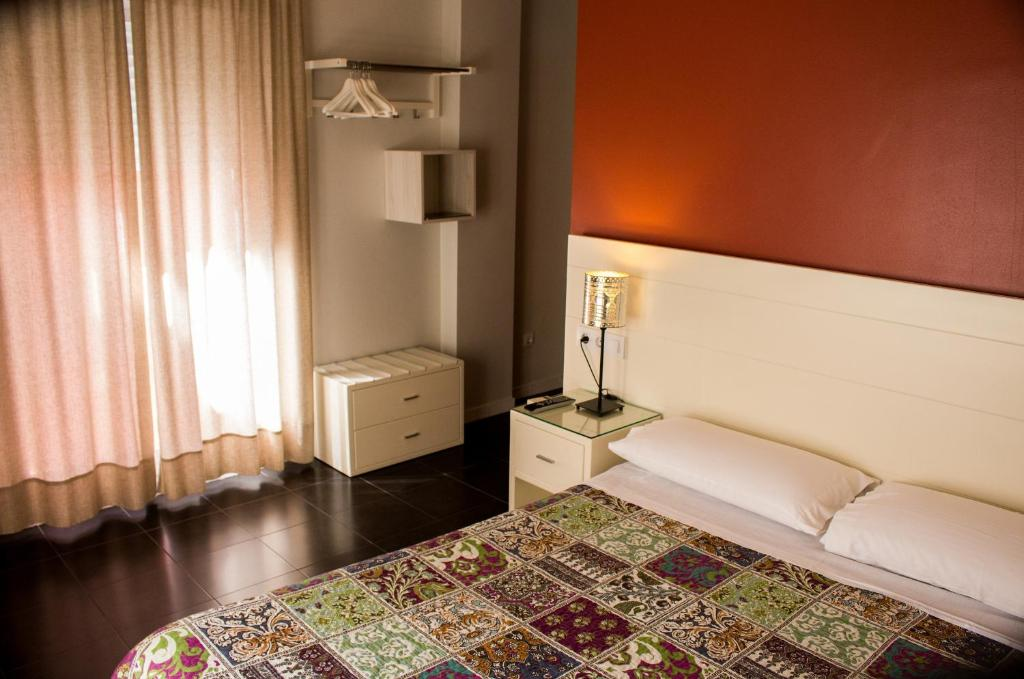 A bed or beds in a room at Hostal San Vicente II