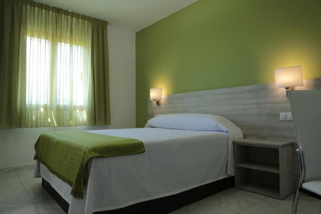 A bed or beds in a room at Hotel Playa de las Catedrales