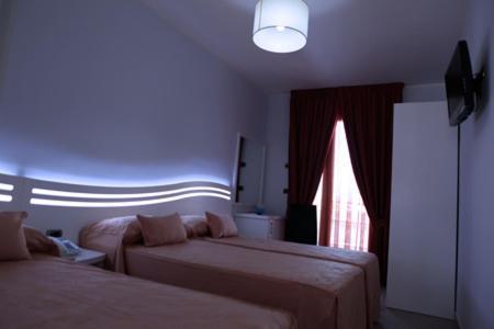 A bed or beds in a room at Hotel Perla Dello Ionio