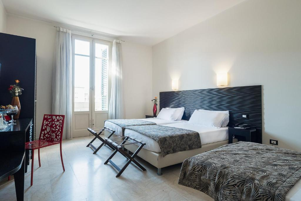 A bed or beds in a room at Hotel Garibaldi