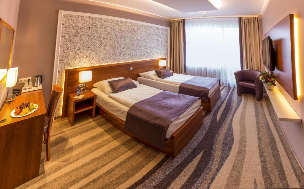 A bed or beds in a room at Avanti Hotel