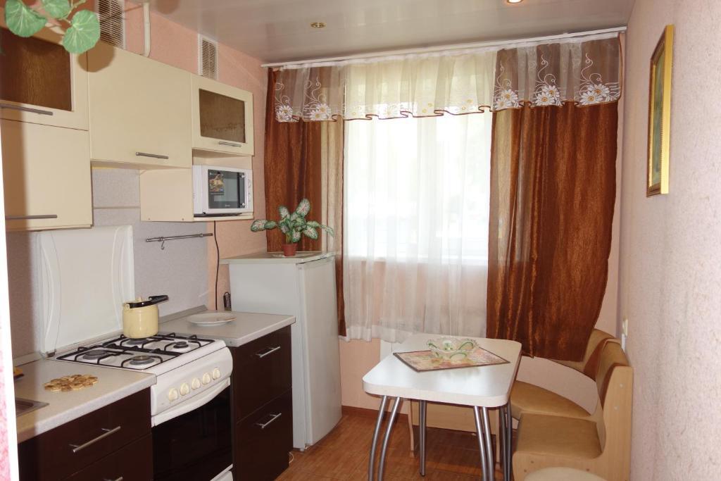 Кухня или мини-кухня в Apartments on Anfinogenova