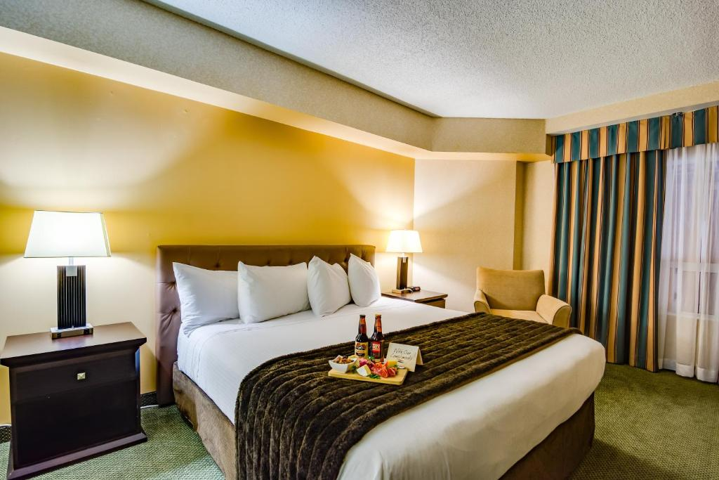 A bed or beds in a room at Sawridge Inn and Conference Centre Edmonton South